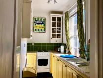 The bright yellow, compact kitchen