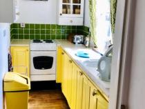 Another view of the bright yellow, compact kitchen